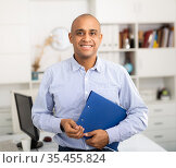 Cheerful business man holding clipboard with papers document write notes. Стоковое фото, фотограф Яков Филимонов / Фотобанк Лори