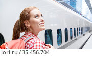 smiling woman with backpack traveling over train. Стоковое фото, фотограф Syda Productions / Фотобанк Лори