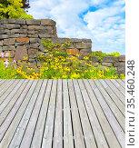 Schöne gepflegte Gartenterrasse mit buntem Blumenbeet und Gartenmauer. Стоковое фото, фотограф Zoonar.com/manfred2000 / easy Fotostock / Фотобанк Лори