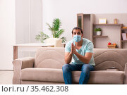 Young man sitting at home during pandemic. Стоковое фото, фотограф Elnur / Фотобанк Лори