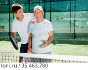 older man and a young man talking on court playing paddle. Стоковое фото, фотограф Татьяна Яцевич / Фотобанк Лори