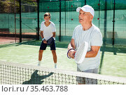 mature man and young man playing padel court. Стоковое фото, фотограф Татьяна Яцевич / Фотобанк Лори