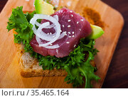 Tasty sandwich with raw tuna, avocado and greens at plate. Стоковое фото, фотограф Яков Филимонов / Фотобанк Лори