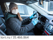 A young woman with mask on her face to avoid infection during flu virus outbreak and coronavirus epidemic, getting ready to go to work by car. Стоковое фото, фотограф Кекяляйнен Андрей / Фотобанк Лори