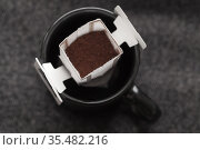 Drip coffee bag is in a black cup, top view, closeup. Стоковое фото, фотограф EugeneSergeev / Фотобанк Лори