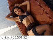 Brunette in lingerie posing in leather armchair. Стоковое фото, фотограф Tryapitsyn Sergiy / Фотобанк Лори