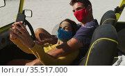 Happy caucasian couple wearing face masks sitting in beach buggy taking selfies. Стоковое видео, агентство Wavebreak Media / Фотобанк Лори