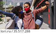 Diverse couple wearing face masks embracing and taking a selfie. Стоковое видео, агентство Wavebreak Media / Фотобанк Лори