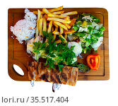 Baked ribs with cheese garnished with rice, french fries and vegetables on a wooden board. Стоковое фото, фотограф Яков Филимонов / Фотобанк Лори