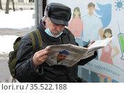 Пожилой мужчина в ожидании городского транспорта читает новости в газете. Масочный режим. Редакционное фото, фотограф Олег Амфитеатров / Фотобанк Лори