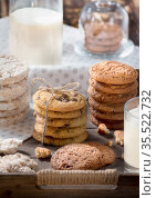 Homemade oatmeal and chocolate chip cookies in rustic wooden tray, glass of milk, bottle, cozy early breakfast concept. Стоковое фото, фотограф Андрей Копылов / Фотобанк Лори