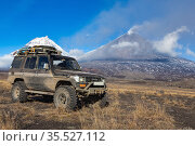 Modified Toyota Land Cruiser Prado in mountain on background eruption active volcano. Japanese SUV modified transmission for off-road expedition (2016 год). Редакционное фото, фотограф А. А. Пирагис / Фотобанк Лори