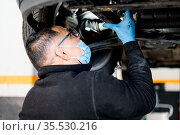 Auto mechanic man with face mask working at auto repair shop. High... Стоковое фото, фотограф Zoonar.com/DAVID HERRAEZ CALZADA / easy Fotostock / Фотобанк Лори