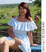 Женщина брюнетка 35 лет в бело-голубом платье сидит на скамейке около плетеного забора на фоне сельского пейзажа. Стоковое фото, фотограф Цибаев Алексей / Фотобанк Лори