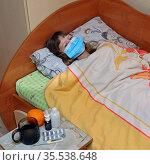 Больная девочка 13 лет лежит в кровати под одеялом, в медицинской маске, рядом лекарства. Стоковое фото, фотограф Цибаев Алексей / Фотобанк Лори