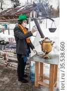 Молодой мужчина в зеленой шляпе с защитной медицинской маской на лице снял трубу с кипящего старинного самовара. Масленичные гулянья на ВДНХ в Москве. Редакционное фото, фотограф Наталья Николаева / Фотобанк Лори