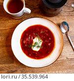 Plate of red borscht garnished with dill and smetana. Стоковое фото, фотограф Яков Филимонов / Фотобанк Лори