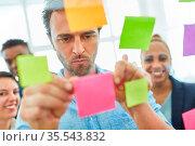 Business Mann klebt Zettel mit Projekt Ideen auf Glas im Brainstorming... Стоковое фото, фотограф Zoonar.com/Robert Kneschke / age Fotostock / Фотобанк Лори