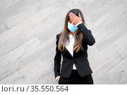 Sick young businesswoman wearing face mask,. Ill female worker having... Стоковое фото, фотограф Zoonar.com/DAVID HERRAEZ CALZADA / easy Fotostock / Фотобанк Лори