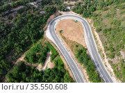 Aerial view of winding road in high mountain pass trough green pine... Стоковое фото, фотограф Zoonar.com/DAVID HERRAEZ CALZADA / easy Fotostock / Фотобанк Лори