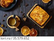 Творожная запеканка и чашка кофе на черном столе. Разбросаны сушенные апельсины и зерна кофе. Вид сверху.  Сервировка завтрака. Стоковое фото, фотограф ирина реброва / Фотобанк Лори
