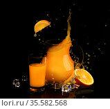Брызги апельсинового сока в кувшине и кубики льда на черном фоне. Стоковое фото, фотограф Марина Володько / Фотобанк Лори