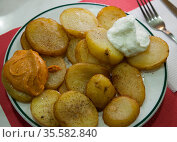 Traditional Spanish fried potatoes Patatas bravas served with cheese sauce and spicy sauce with paprika and chili. Стоковое фото, фотограф Яков Филимонов / Фотобанк Лори