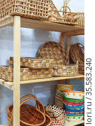 Eco-friendly goods, home space organization and storage, various natural straw wicker baskets stand on a shelf on a wooden rack in a shop window on sale. Редакционное фото, фотограф Светлана Евграфова / Фотобанк Лори