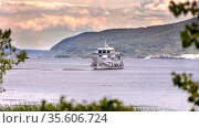 Russia Samara August 2020: A small pleasure ship stands on a sandbank in the middle of the Volga River against the backdrop of the Zhiguli mountains on a summer evening. Редакционное фото, фотограф Акиньшин Владимир / Фотобанк Лори
