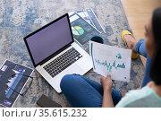 Mixed race gender fluid man working at home sitting on floor using laptop, copy space screen. Стоковое фото, агентство Wavebreak Media / Фотобанк Лори