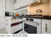Luxurious white modern kitchen interior, drawers pulled out, dishwasher's door open. Стоковое фото, фотограф Сергей Старуш / Фотобанк Лори