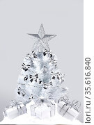White christmas tree with silver decorations and gifts on snow on... Стоковое фото, фотограф Zoonar.com/Ivan Mikhaylov / easy Fotostock / Фотобанк Лори