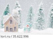 Small decorative snowman near wooden house in fir forest under falling... Стоковое фото, фотограф Zoonar.com/Ivan Mikhaylov / easy Fotostock / Фотобанк Лори