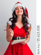 Pretty smiling pin-up Santa girl with wish list letter and red pencil. Стоковое фото, фотограф Zoonar.com/Ivan Mikhaylov / easy Fotostock / Фотобанк Лори
