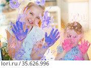 Zwei Mädchen malen viele Handabdrücke mit Fingerfarbe an eine Scheibe. Стоковое фото, фотограф Zoonar.com/Robert Kneschke / age Fotostock / Фотобанк Лори