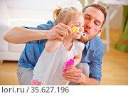 Vater und Tochter pusten gemeinsam Seifenblasen zu Hause. Стоковое фото, фотограф Zoonar.com/Robert Kneschke / age Fotostock / Фотобанк Лори