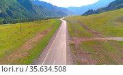 Flight over mountain asphalt highway road and meadow. Стоковое видео, видеограф Александр Маркин / Фотобанк Лори