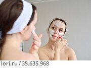 The girl applies a cosmetic mask in front of the mirror. Стоковое фото, фотограф Арестов Андрей Павлович / Фотобанк Лори