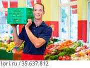 Lächelnder Supermarkt-Mitarbeiter trägt eine Kiste mit Obst. Стоковое фото, фотограф Zoonar.com/Robert Kneschke / age Fotostock / Фотобанк Лори