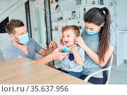 Eltern und weinendes Kind mit Mund-Nasen-Schutz wegen Coronavirus... Стоковое фото, фотограф Zoonar.com/Robert Kneschke / age Fotostock / Фотобанк Лори