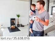 Vater hält seinen Sohn auf dem Arm und spielt mit ihm Ball im Wohnzimmer. Стоковое фото, фотограф Zoonar.com/Robert Kneschke / age Fotostock / Фотобанк Лори