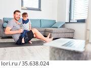 Vater und Kind im Wohnzimmer spielen zusammen bei Videochat am Laptop... Стоковое фото, фотограф Zoonar.com/Robert Kneschke / age Fotostock / Фотобанк Лори
