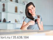 Fröhliche junge Frau mit Schere zu Hause beim selber schneiden ihrer... Стоковое фото, фотограф Zoonar.com/Robert Kneschke / age Fotostock / Фотобанк Лори