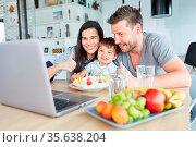 Familie feiert Geburtstag mit Kind und isst eine Torte am Laptop ... Стоковое фото, фотограф Zoonar.com/Robert Kneschke / age Fotostock / Фотобанк Лори