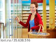 Ältere lächelnde Frau steht im Supermarkt am Kühlregal. Стоковое фото, фотограф Zoonar.com/Robert Kneschke / age Fotostock / Фотобанк Лори