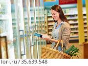 Junge Frau mit Einkaufskorb nimmt Tiefkühlkost aus Kühlregal im Supermarkt. Стоковое фото, фотограф Zoonar.com/Robert Kneschke / age Fotostock / Фотобанк Лори