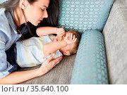 Mutter kümmert sich liebevoll um müdes Kind auf dem Sofa im Wohnzimmer. Стоковое фото, фотограф Zoonar.com/Robert Kneschke / age Fotostock / Фотобанк Лори