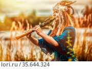Beautiful shamanic girl playing on shaman flute in the nature. Стоковое фото, фотограф Zoonar.com/Jozef Klopacka / easy Fotostock / Фотобанк Лори