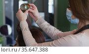 Female hairdresser wearing face mask putting rollers on hair of female customer at hair salon. Стоковое видео, агентство Wavebreak Media / Фотобанк Лори