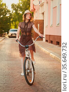 Young woman in hat and dress moves on bike at old european city, sunset... Стоковое фото, фотограф Zoonar.com/A.Tugolukov / easy Fotostock / Фотобанк Лори